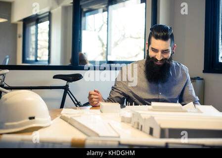 Architect looking at model building, smiling cheerfully - Stock Image