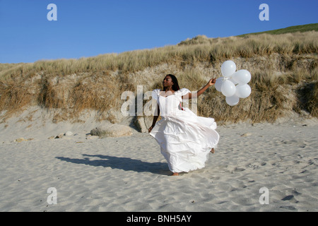 African Woman with Dreadlocks, Wearing a White Wedding Dress, Holding Balloons and Standing on the Beach by Sand - Stock Image