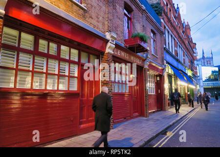 People walking on street passing shops in Southwark, London, England, UK - Stock Image