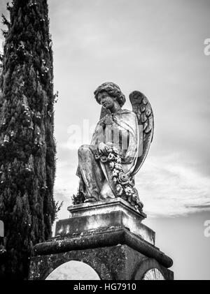 A kneeling angel statue in weathered stone keeps watch over a grave beneath. - Stock Image