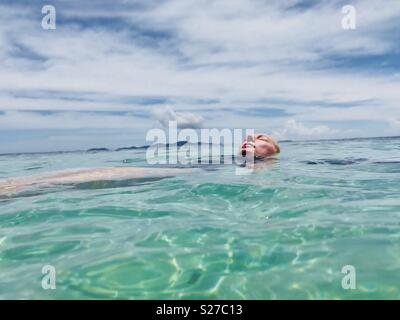 A young women floating in the ocean. Tavarua Island resort, Fiji. - Stock Image