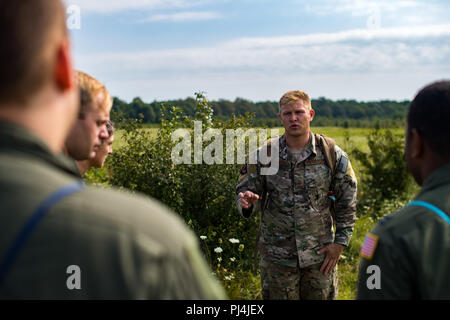 U.S. Air Force Staff Sgt. Christian Martin, 86th Operations Support Squadron Survival, Evasion, Rescue, and Escape specialist, briefs 37th Airlift Squadron pilots on their SERE scenario in Bolovani, Romania, Aug. 24, 2018. The Airmen worked with Romanian air force pilots during the training as part of Carpathian Summer 2018. (U.S. Air Force photo by Senior Airman Devin Boyer) - Stock Image