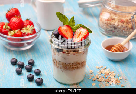 healthy breakfast. yogurt with granola, fresh berries on a blue wooden background - Stock Image