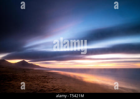 Beautiful landscape in long exposure at the beach during coloured cloudy sunset with mountains in background - wild and scenic vacation concept - cute - Stock Image