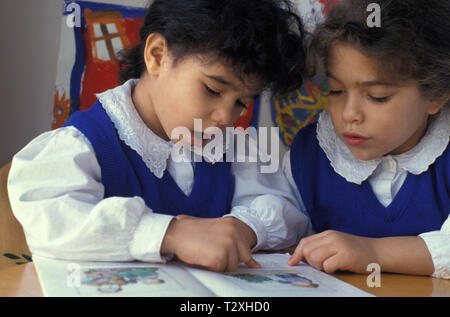 two little girls reading out loud in class - Stock Image