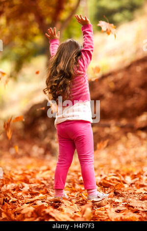 Happy little girl in autumn park, rear view of a nice child throwing up dry tree leaves, playing outdoors in a warm - Stock Image