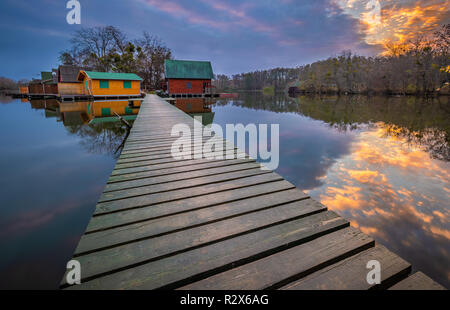Tata, Hungary - Fishing cottages on small island at Lake Darito (Derito to) at sunset with amazing sky and clouds and pier - Stock Image