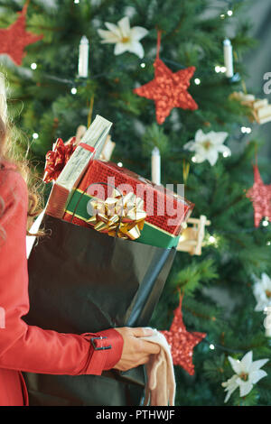 Closeup on modern woman in red trench coat with shopping bag full of Christmas present boxes near Christmas tree - Stock Image