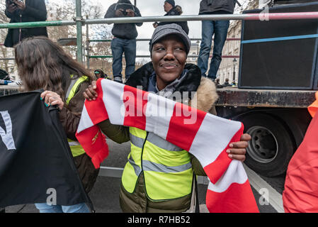 London, UK. 9th Dec, 2018. A woman stands with a scarf in front of the stage in Whitehall for the rally by united anti-fascists in opposition to Tommy Robinson's fascist pro-Brexit march. The protesters including both remain and leave supporting anti-fascists had gathered at the BBC to to to the rally at Downing St. Police had issued conditions on both events designed to keep the two groups well apart. Credit: Peter Marshall/Alamy Live News - Stock Image