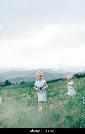 Girls walking in meadow - Stock Image