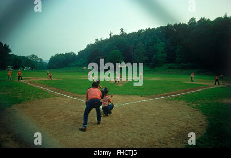 Little leaguers playing on old dirt country baseball diamond in Middle America - Stock Image