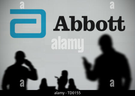 The Abbott Laboratories logo is seen on an LED screen in the background while a silhouetted person uses a smartphone in the foreground (Editorial use - Stock Image
