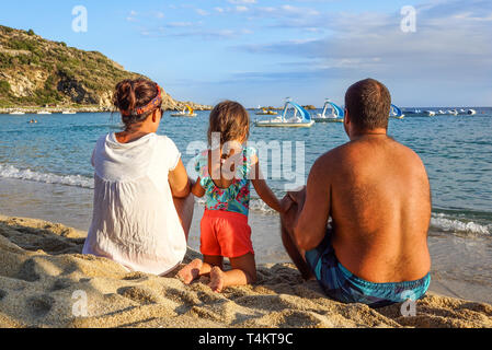 Happy family on the beach. People having fun on summer vacation. Father, mother and child against blue sea and sky background. Holiday travel concept - Stock Image