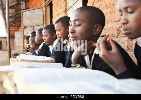 group of young Ugandan school children in smart uniforms sit on wooden benches outside their brick classrooms in Uganda reading text books - Stock Image