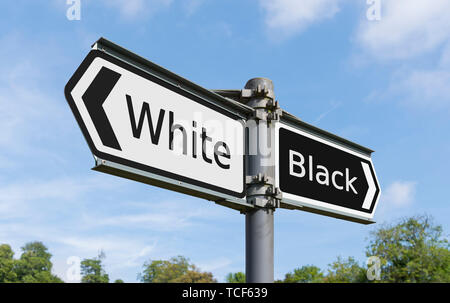 White & Black concept sign pointing in opposite directions, to illustrate racial segregation or discrimination. Racist. Racism..Prejudice. Prejudices. - Stock Image