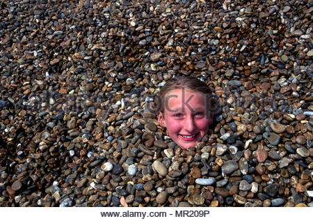 Girl child female buried in shingle on beach just her head showing above the pebbles - Stock Image