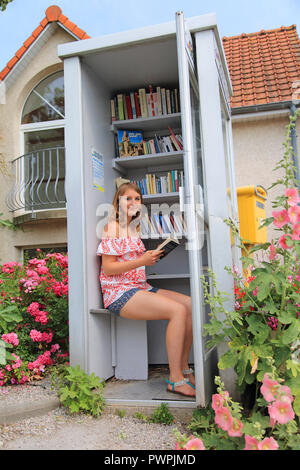French, young woman and old telephone booth turned into a free library - Stock Image