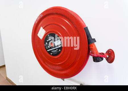 Red fire hose on wall inside building. - Stock Image