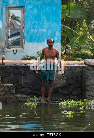 Vertical portrait of a man having a wash on the riverbank in Alleppy, India - Stock Image