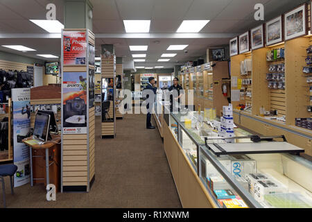 Camera salesperson helping a customer in Kerrisdale Cameras store on West 41st Avenue in Kerrisdale, Vancouver, BC, Canada - Stock Image