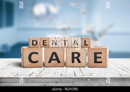 Dental care sign on a table at a dentist with a blurry blue room in the background - Stock Image