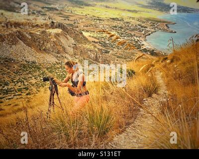 Young woman taking photo with camera in mountain - Stock Image