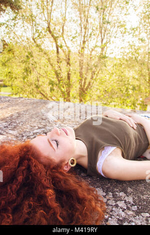 Beautiful young and redhead woman enjoying a spring day outdoors - Stock Image