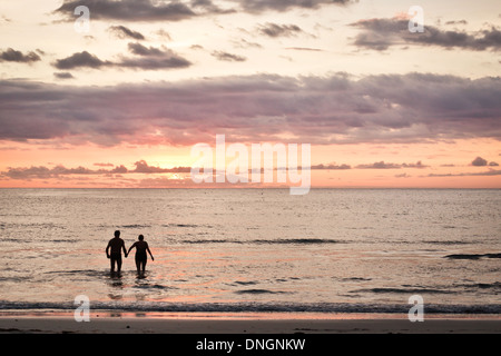 A couple entering the sea at sunset - Stock Image