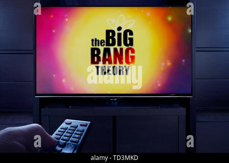 A man points a TV remote at the television which displays the Big Bang Theory main title screen (Editorial use only). - Stock Image