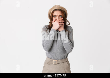Portrait closeup of scared woman 30s wearing hat terrifying and covering mouth isolated over white background - Stock Image
