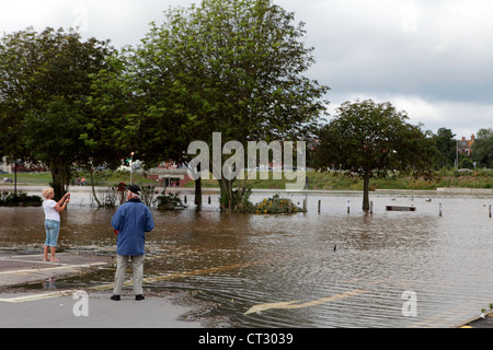 Locals in Weymouth Dorset inspect the flooded waters in July 2012, the month when the sailing Olympics come to town - Stock Image