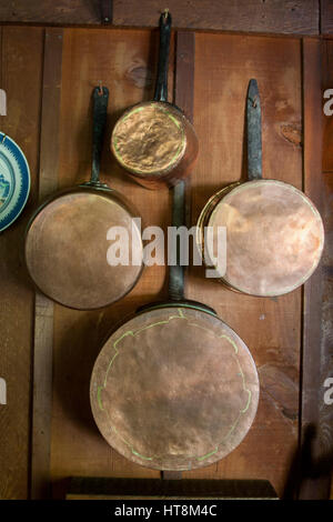 Antique copper pots hanging on the wall in the dining room of Deetjen's Big Sur Inn, in Big Sur, Caliofrnia. - Stock Image