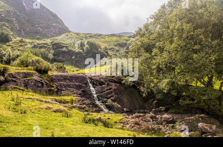 Picturesgue valley in Gleninchaquin Park with small brook flowing down on rock.County Kerry,Ireland. - Stock Image