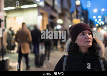 Woman in warm clothing standing on urban sidewalk at night - Stock Image