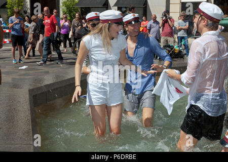 Copenhagen, Denmark. June 29, 2018. Free, sponsored towels from a nearby bank are most welcome after the plunge. Danish students celebrate their high school graduation and take the plunge. A dance around and a dip or dive into the cold water of the Stork Fountain (Storkespringvandet) on the pedestrian street, Stroeget, is a traditional element on the day of celebration for  graduated students in Greater Copenhagen. It is often part of the long, exhausting and high-spirited truck tour visiting each student's home for refreshments. Credit: Niels Quist/Alamy Live News - Stock Image