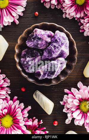 Amethyst with Moonstone and Pink Mums on Dark Wood - Stock Image