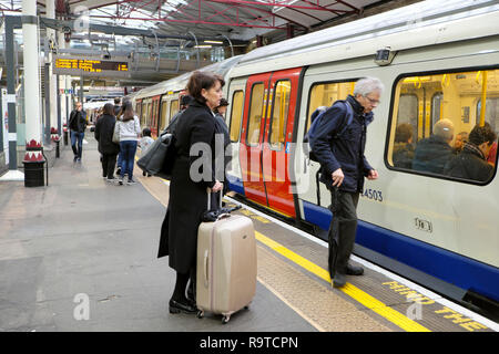 People waiting on the platform with luggage boarding a Hammersmith and City tube train in an underground station in London England UK  KATHY DEWITT - Stock Image
