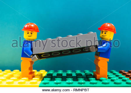 Poznan, Poland - February 13, 2019: Two Lego construction workers with helmet lifting together as a team a gray plastic brick. Teamwork is very helpfu - Stock Image