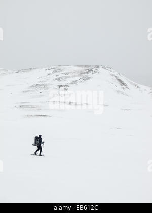 man  with heavy pack in the distance snowshoeing through a winter mountain landscape with mountain top behind - Stock Image