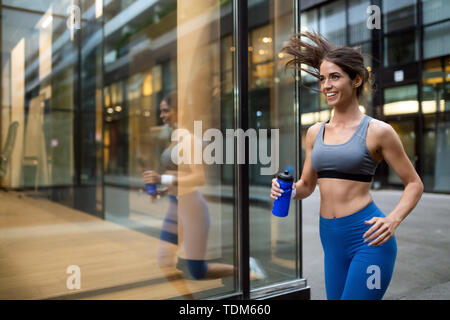 Young happy woman runner jogging in city outdoor - Stock Image