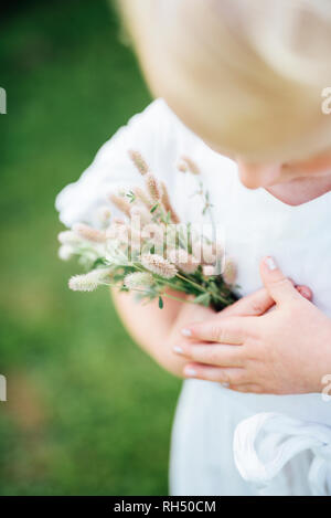 Girl holding wildflowers, close-up - Stock Image