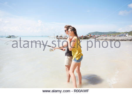 Young couple fishing on beach - Stock Image