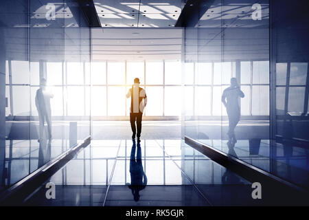 Man walks and speaks by mobile phone atbig office hall with reflections. Businessman concept - Stock Image