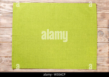 green cloth napkin on brown rustic wooden background top view with copy space. - Stock Image