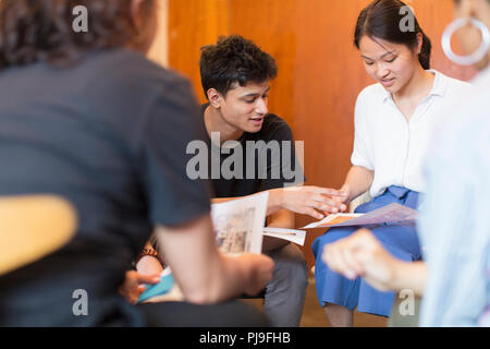 Creative designers reviewing proofs in meeting - Stock Image
