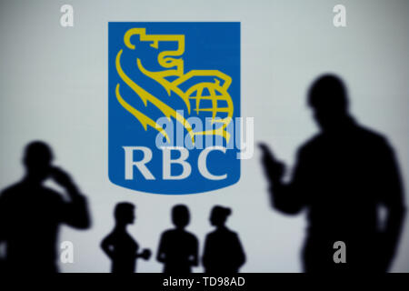 The RBC Royal Bank logo is seen on an LED screen in the background while a silhouetted person uses a smartphone (Editorial use only) - Stock Image