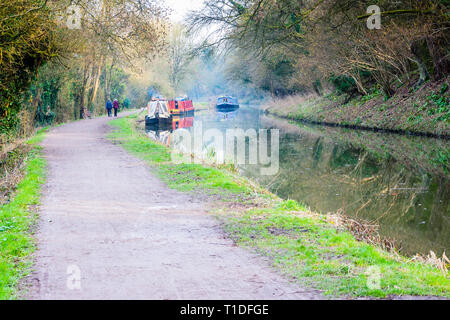 A Couple walking along the towpath of the Kennet and Avon canal passing houseboats with a haze from the chimneys of the boats on a bright spring day. - Stock Image