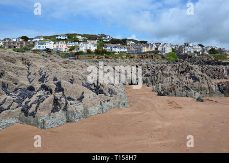 Craggy rocks on Woolacombe Beach with a view of hotels, seafront apartments, and other buildings, from Woolacombe Bay, Devon, UK - Stock Image