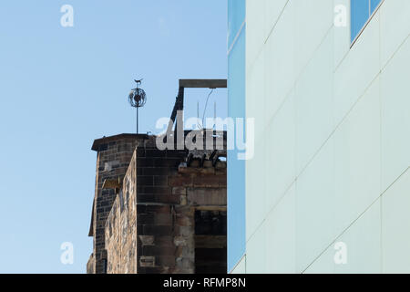 weather vane  wrought iron finial above fire damaged walls of glasgow school of art - repair work from first fire can be seen, Glasgow, Scotland, UK - Stock Image