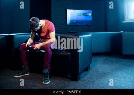 Man losing in video game sitting on the couch with sad emotions in the dark room of the playing club - Stock Image
